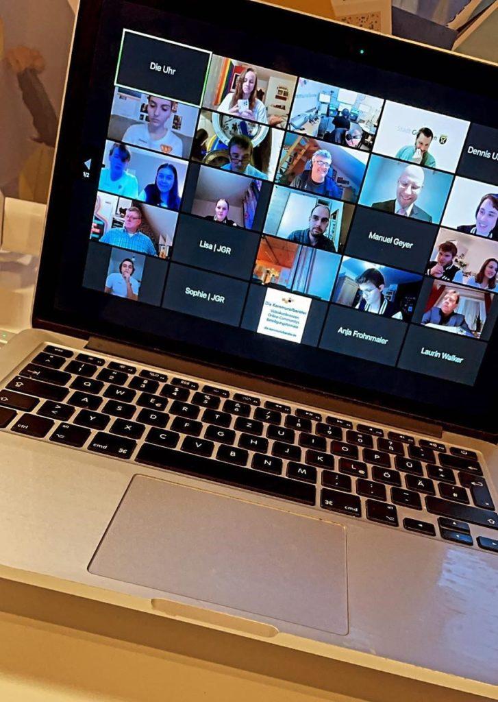 Laptop mit geöffneter Zoom-Konferenz. Die Teilnehmenden sind in kleinen Kacheln abgebildet
